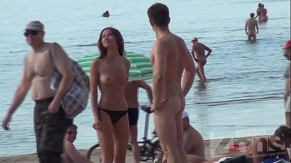 Topless brunette on a nude beach with nice tits.